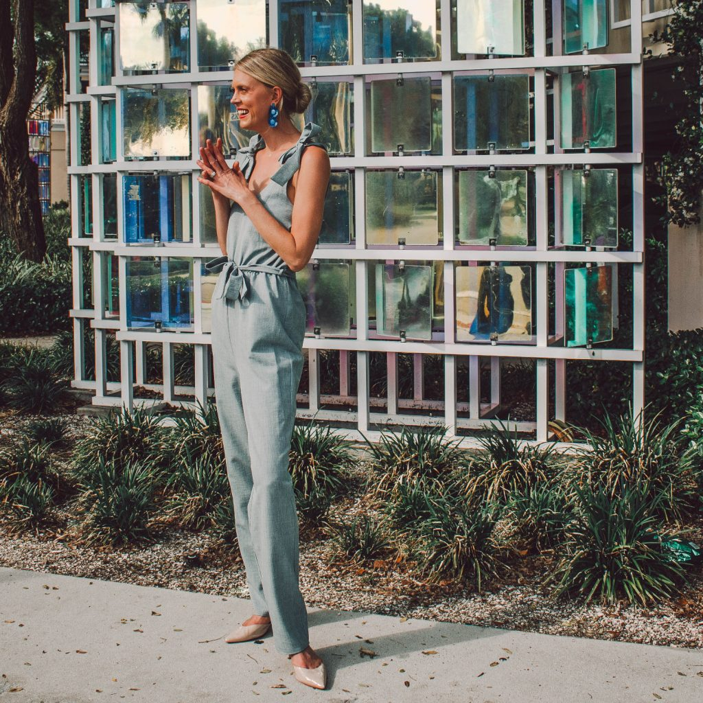 A tall chambray blue jumpsuit with shoulder ties and a tie waist